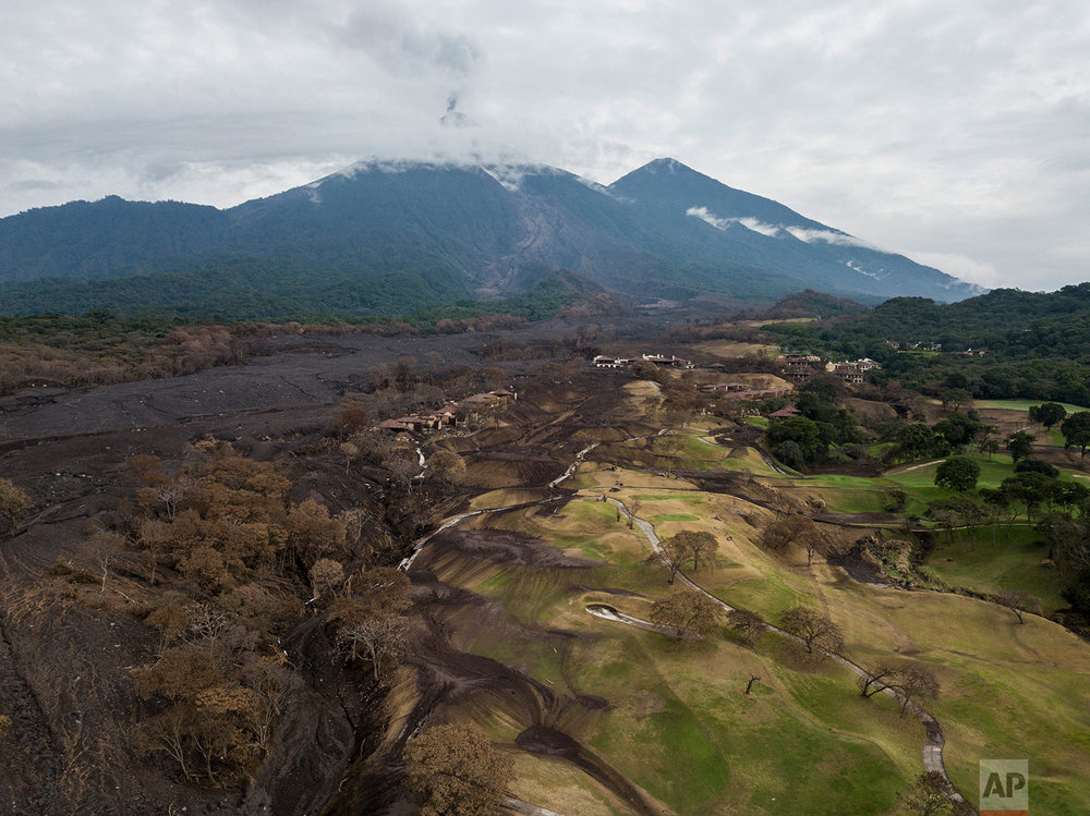 In this June 16, 2018 photo, black volcanic debris covers parts of La Reunion Golf Resort & Residences, after the eruption of the Volcano of Fire, top, in San Miguel Los Lotes, Guatemala. (AP Photo/Rodrigo Abd)