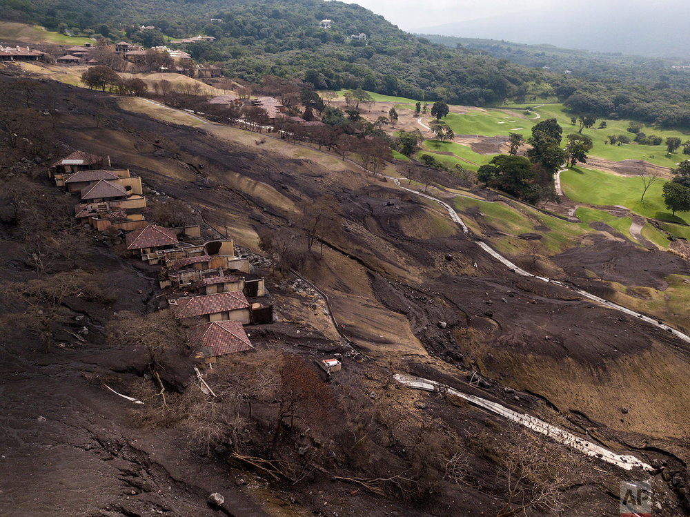 In this June 19, 2018 photo, homes are surrounded by volcanic debris at La Reunion Golf Resort & Residences, destroyed by the eruption of the Volcano of Fire, top, in San Miguel Los Lotes, Guatemala. (AP Photo/Rodrigo Abd)