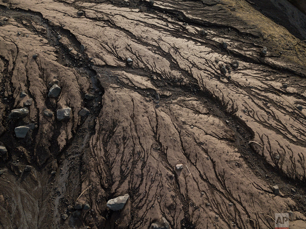 This June 18, 2018 photo taken from high above makes large boulders look like small rocks in the aftermath of the eruption of the Volcano of Fire in San Miguel Los Lotes, Guatemala. (AP Photo/Rodrigo Abd)