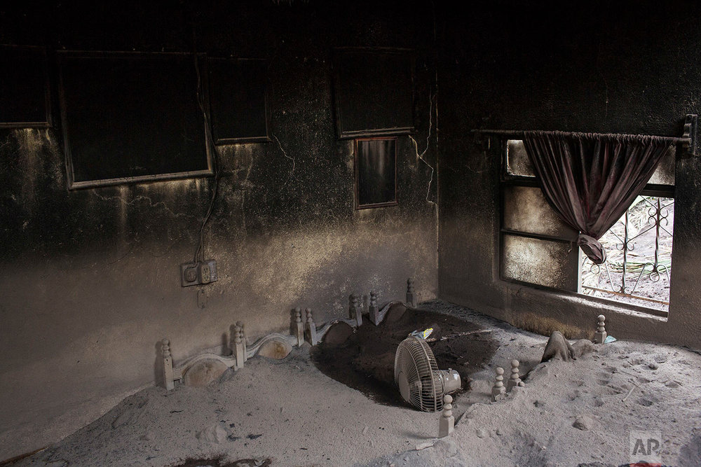 A dining room is interred in volcanic ash spewed by the Volcano of Fire in San Miguel Los Lotes, Guatemala, June 8, 2018. (AP Photo/Rodrigo Abd)