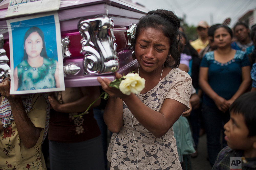 Yoselin Rancho cries as she carries the remains of her best friend Etelvina Charal, who died during the eruption of the Volcano of Fire in San Juan Alotenango, Guatemala, June 10, 2018. (AP Photo/Rodrigo Abd)