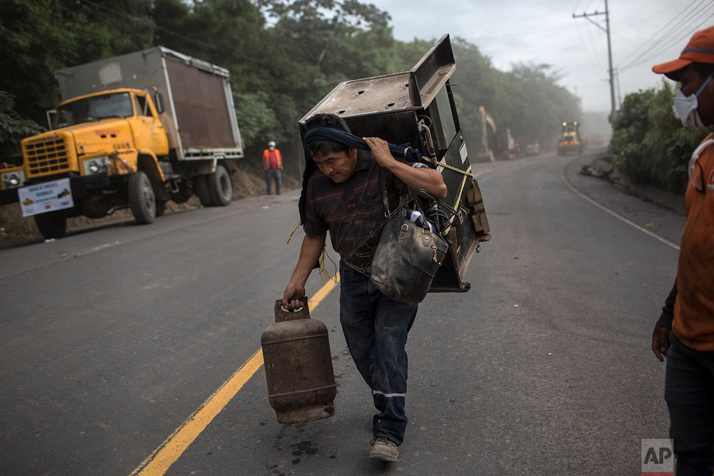 A resident carries a stove and gas can recovered from his volcano-destroyed home, following the eruption of the Volcano of Fire in San Miguel Los Lotes, Guatemala, June 10, 2018. (AP Photo/Rodrigo Abd)
