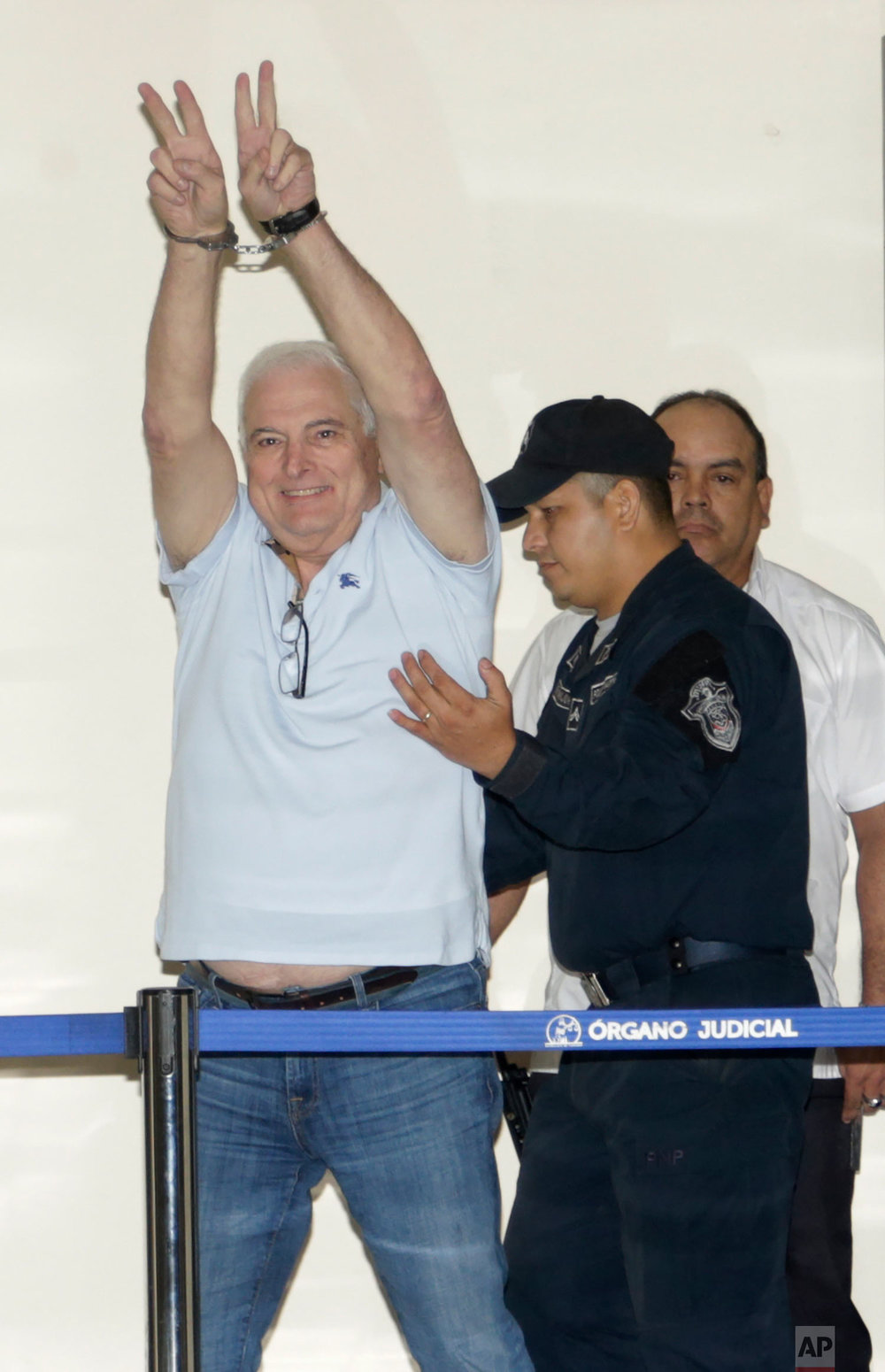 Former Panamanian President Ricardo Martinelli gestures victory from his handcuffs while escorted away from his hearing at the Supreme Court in Panama City, June 11, 2018. Martinelli returned to Panama to face political espionage and embezzlement charges after being extradited from the U.S. (AP Photo/Arnulfo Franco)