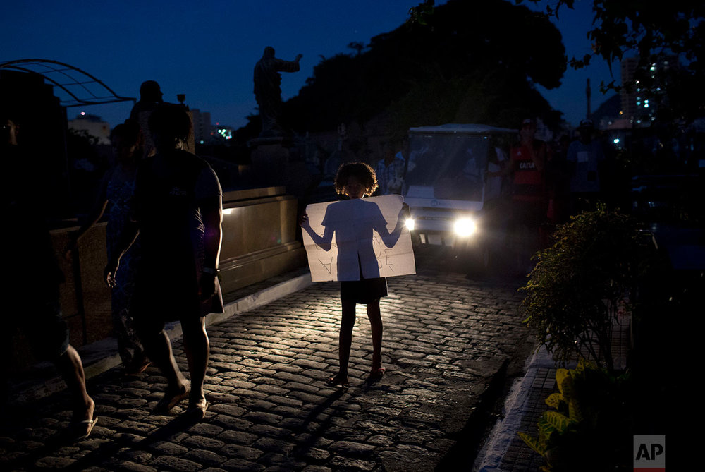A child holds a sign protesting the death of teenager Marcos Vinicius da Silva, illuminated by the headlights of the vehicle transporting the coffin containing his remains to a cemetery in Rio de Janeiro, Brazil, June 21, 2018. Da Silva is one of two 14-year-olds killed by stray bullets in Rio on Wednesday. (AP Photo/Silvia Izquierdo)