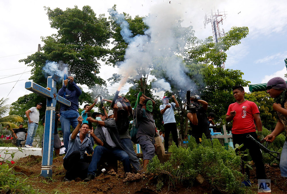 Anti-government protesters shoot their homemade weapons as they bury a fellow protester, Jorge Zepeda who was killed during a demonstration, at the cemetery in Monimbo, Nicaragua, June 7, 2018. (AP Photo/Alfredo Zuniga)