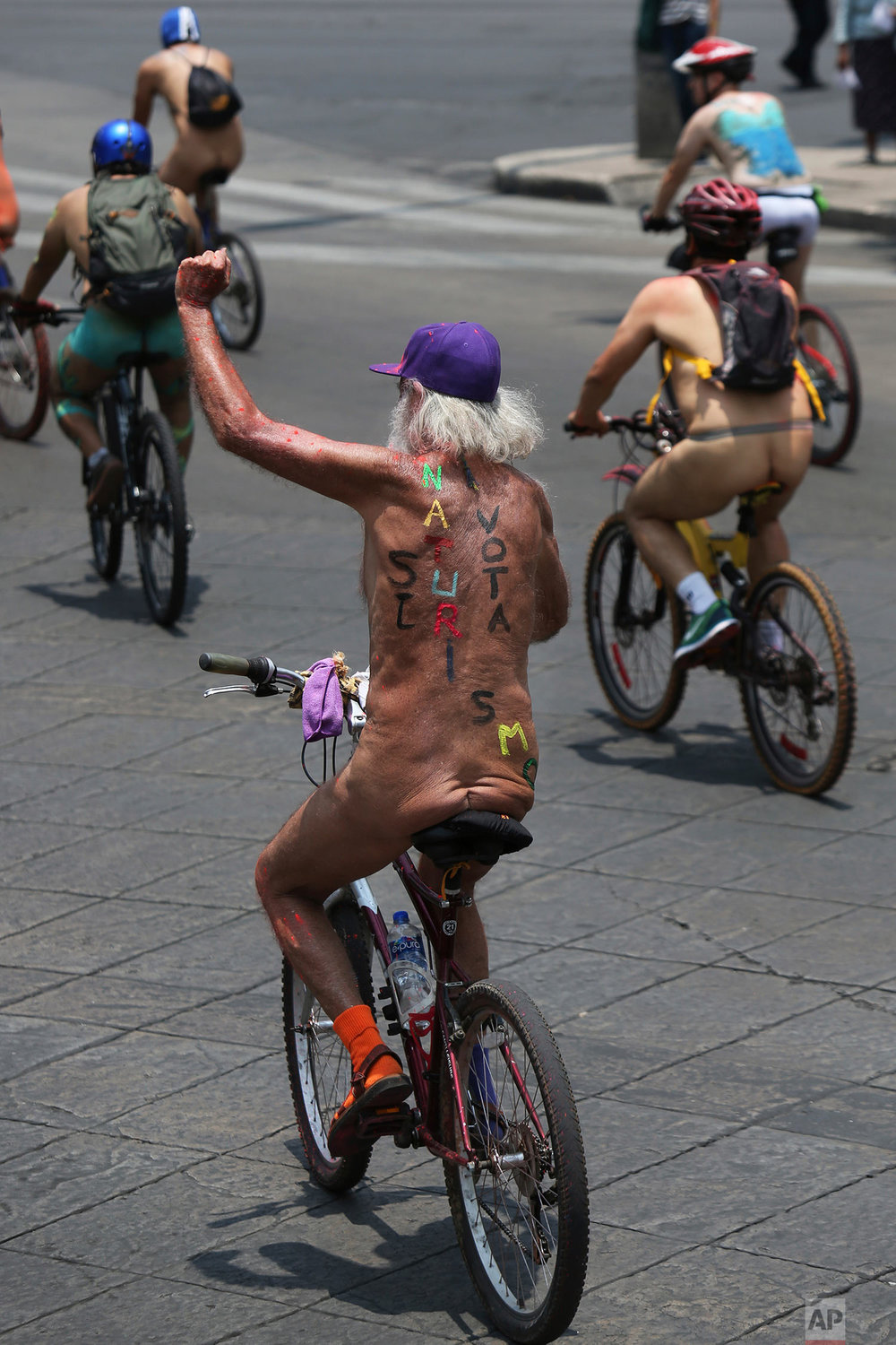 Nude cyclists rides through Mexico City, June 9, 2018, to promote the use of bicycles and highlight damage caused by car dependency. (AP Photo/Marco Ugarte)