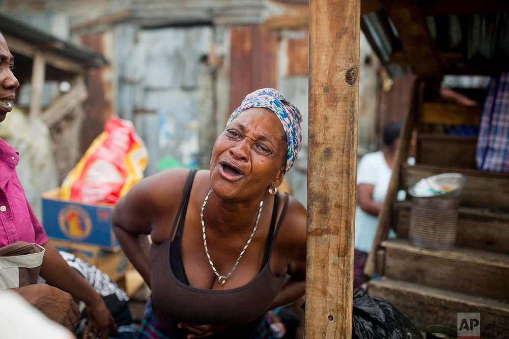 A woman cries after a fire wiped out her stall at a rice and beans market in Port-au-Prince, Haiti, June 12, 2018. The entire market, where vendors sell rice, black beans, onions and other grains and perishables was destroyed. (AP Photo/Dieu Nalio Chery)