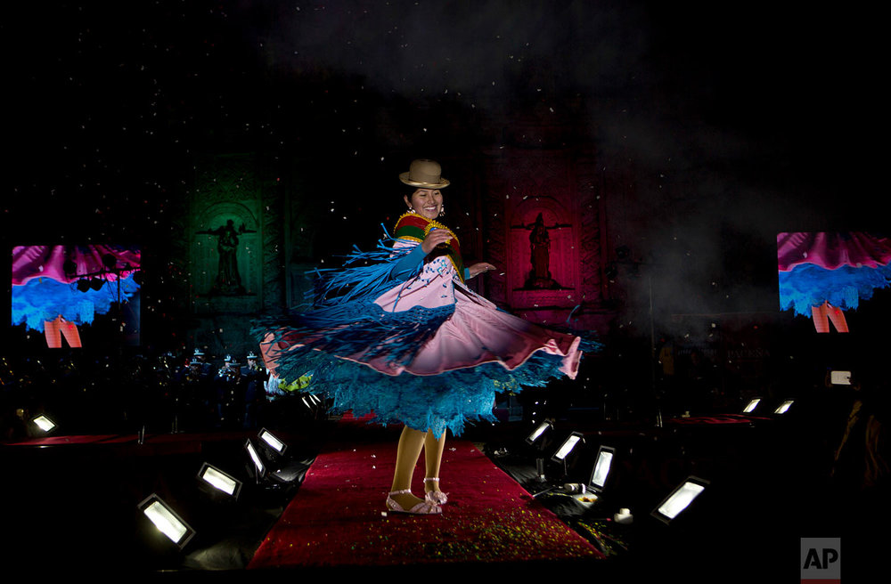 A woman turns on the catwalk during Miss Cholita beauty pageant in La Paz, Bolivia, June 29, 2018, an annual contest recognizing indigenous women's fashion, beauty, command of indigenous lifestyle and language. (AP Photo/Juan Karita)