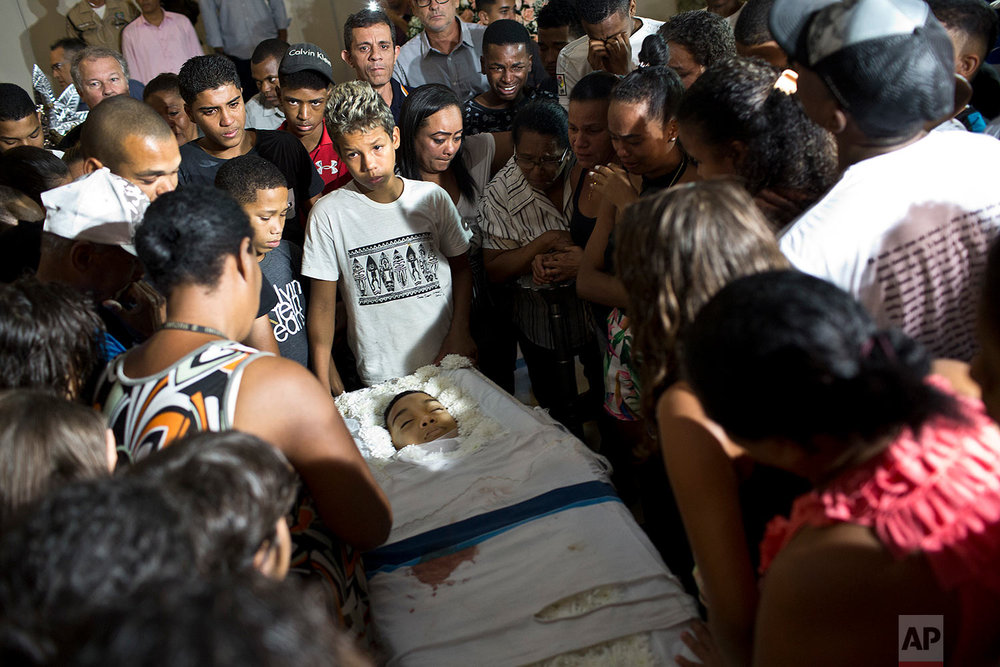 Relatives and friends of Marcos Vinicius da Silva attend his wake in Rio de Janeiro, Brazil, June 21, 2018. Da Silva is one of two 14-year-olds killed by stray bullets in Rio on Wednesday. (AP Photo/Silvia Izquierdo)