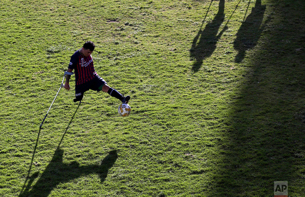 Robin Burbano controls the ball on crutches, during a game against El Empalme at a national soccer tournament for players with amputated limbs, in Quito, Ecuador, June 9, 2018. (AP Photo/Dolores Ochoa)