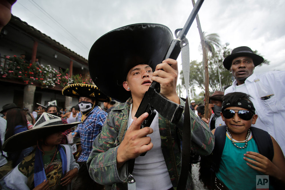 Indigenous men in costume, one holding a mock gun made of wood, dance to the rhythm of the monotonous tune of San Juanito, as groups from different communities compete to occupy the main plaza during the Sun Festival in Cotacachi, Ecuador, June 24, 2018. Across the Andes, from the tip of Argentina as far north as Colombia, indigenous communities are gathering for the southern hemisphere's winter solstice to honor the ancient sun god. (AP Photo/Dolores Ochoa)