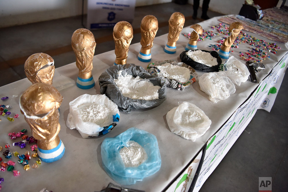 This photo released by the National Security Ministry shows fake World Cup trophies stuffed with cocaine, and the product itself on display next to the trophies, in Buenos Aires, Argentina, June 21, 2018 photo. (National Security Ministry via AP)