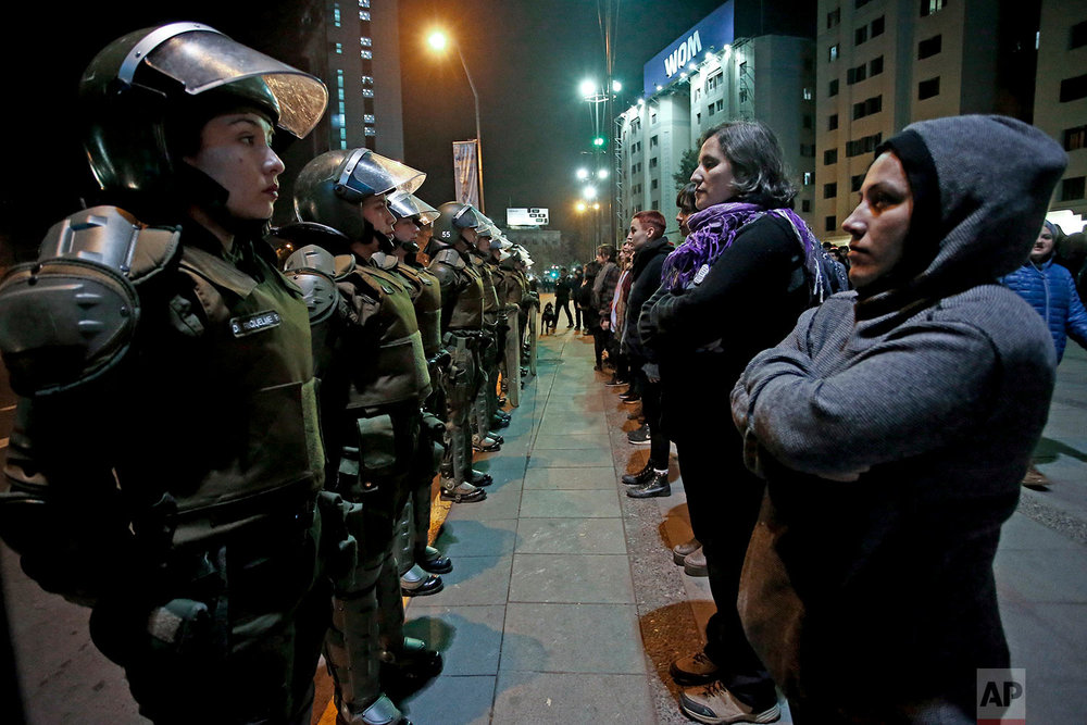 In this June 1, 2018 photo, women face a line of policewomen at the start of a feminist march in Santiago, Chile. 