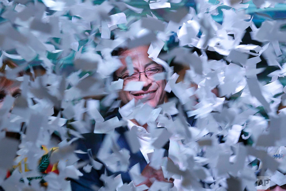 Presidential candidate Gustavo Petro is surrounded in ticker tape as he speaks to supporters after his rival Ivan Duque won the election in Bogota, Colombia, June 17, 2018. (AP Photo/Martin Mejia)
