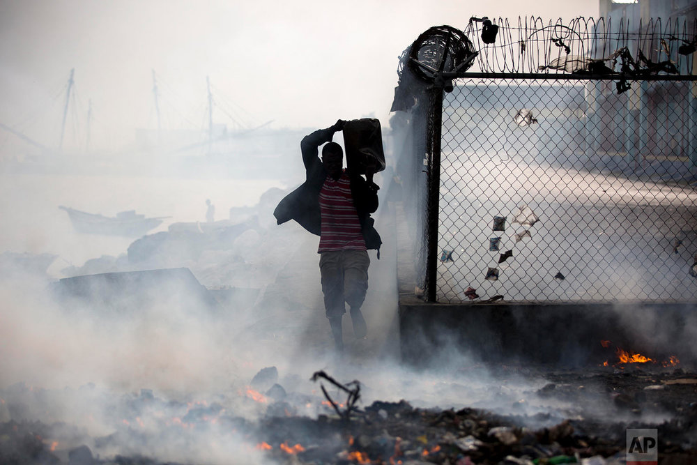 A man carries a container of sea water past burning trash at the harbor in Port-au-Prince, Haiti, June 7, 2018, to keep the fire from burning his merchandise. (AP Photo/Dieu Nalio Chery)