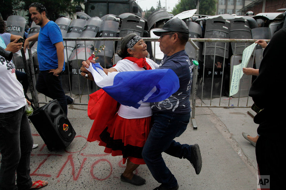 A couple dances in front of a police barricade during a protest in Tegucigalpa, Honduras, June 2, 2018, during a protest against Juan Orlando Hernandez' government before they were forcibly removed by military and police. (AP Photo/Fernando Antonio)