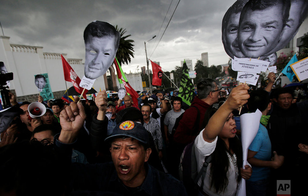 Supporters of Ecuador's former President Rafael Correa hold up his image to protest an attempt to prosecute him in connection with the attempted kidnapping of opposition lawmaker, in Quito, Ecuador, June 14, 2018. (AP Photo/Dolores Ochoa)