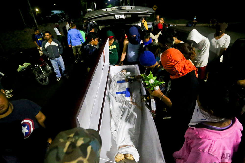 The body of 19-year-old Chester Chavarria is surrounded by his friends outside the Autonomous University of Nicaragua, in Managua, June 8, 2018. Chavarria died after being shot several times while guarding a barricade during a protest against the government. (AP Photo/Esteban Felix)