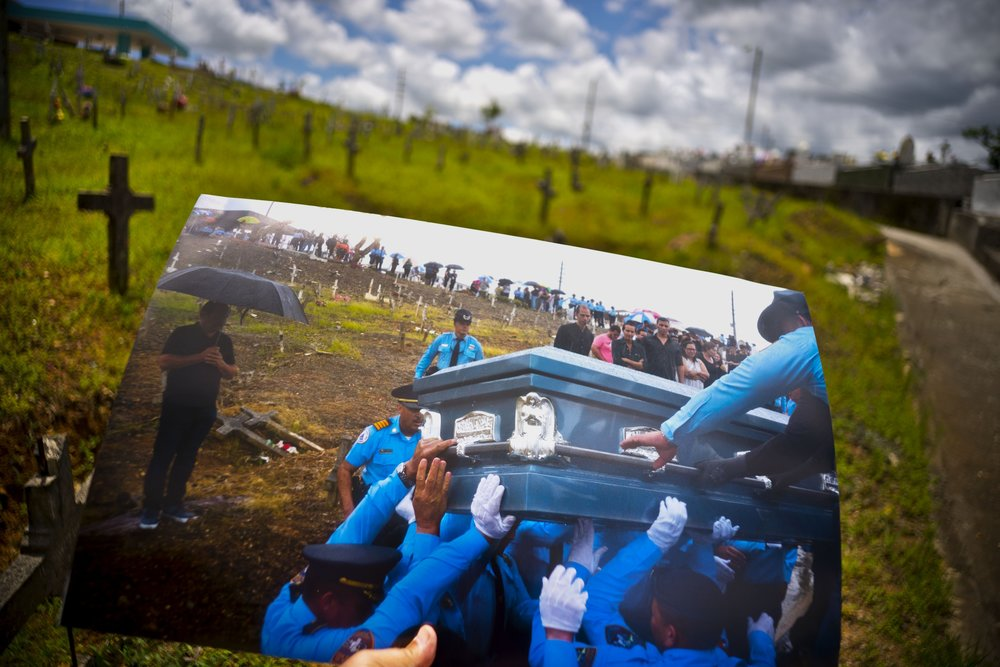 A printed photo taken on Sept. 29, 2017 showing police lifting the coffin of officer Luis Angel Gonzalez Lorenzo, who was killed during the passage of Hurricane Maria when he tried to cross a river in his car, is shown at the same cemetery in Aguada, Puerto Rico, May 31, 2018. The local police force of Aguadilla and Aguada lacks about a dozen officers since the storm, due to resignations and retirements. The U.S. territory's bankruptcy has frozen promotions, salaries, new hires and some police academies have even closed. (AP Photo/Ramon Espinosa)