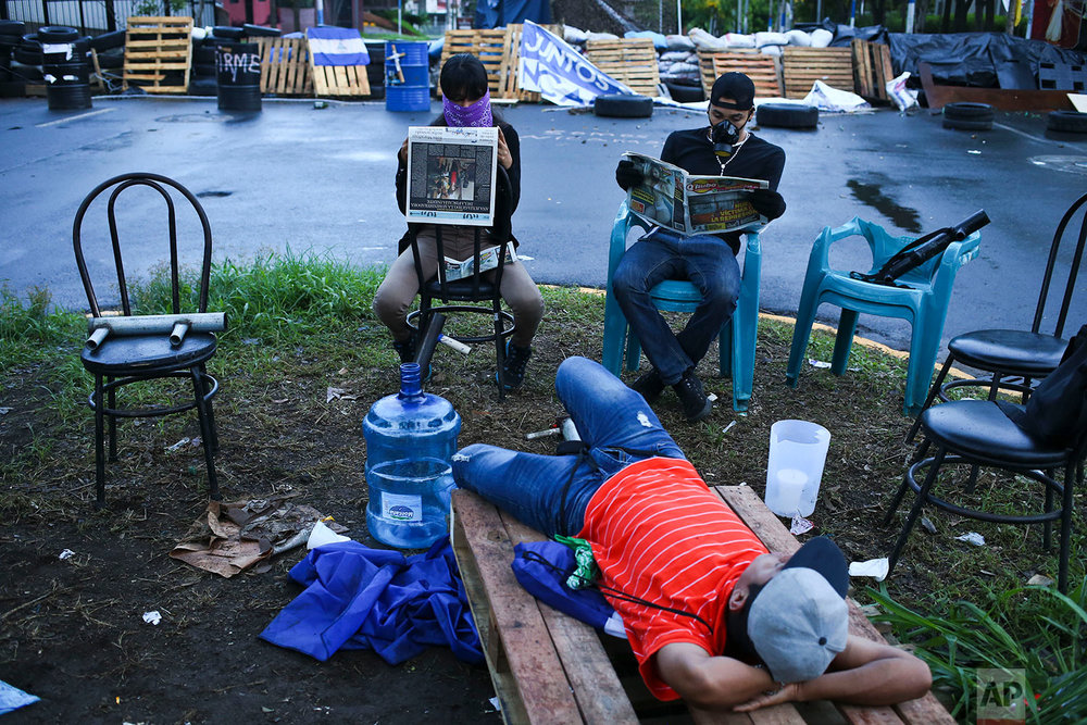Anti-government students keep watch at their barricade at one of the entrances to the Autonomous University of Nicaragua. (AP Photo/Esteban Felix)
