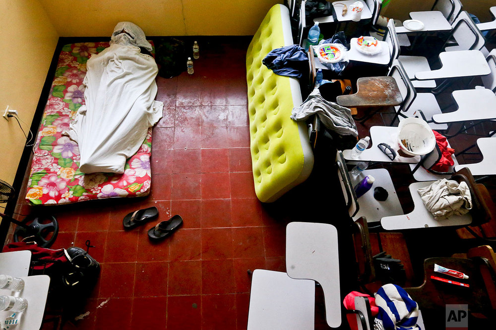 In this June 8, 2018 photo, a university student sleeps inside a classroom at the Autonomous University of Nicaragua where anti-government students have barricaded themselves on campus for protection from government security forces and armed supporters in Managua, Nicaragua. (AP Photo/Esteban Felix)
