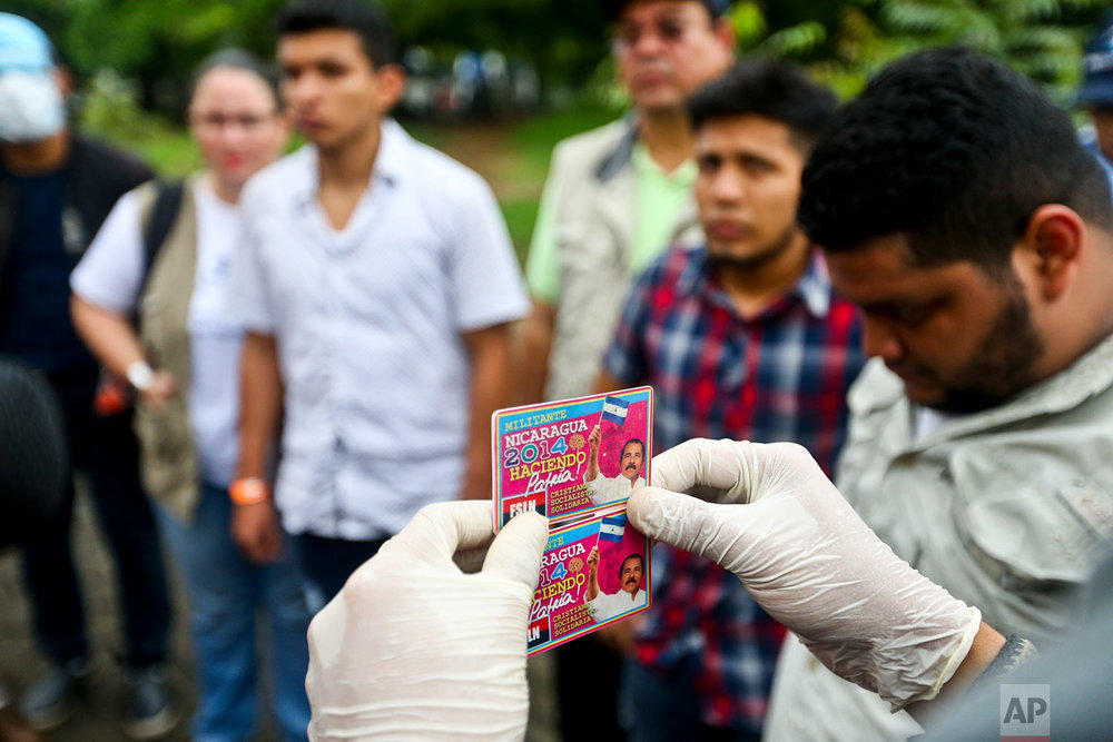 In this May 27, 2018 photo, an identification card for a Sandinista National Liberation Front militant, confiscated from one of the three men behind, is held up as the alleged infiltrators are detained by anti-government students at the Autonomous University of Nicaragua in Managua, Nicaragua. (AP Photo/Esteban Felix)