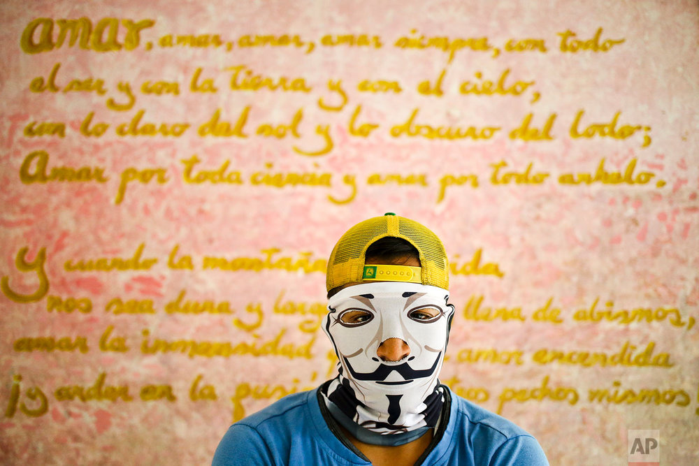 In this June 9, 2018 photo, a university student poses by a wall decorated with a poem by Nicaraguan poet Ruben Dario at the Autonomous University of Nicaragua school where students have barricaded themselves on campus for protection from government security forces and armed supporters in Managua, Nicaragua. (AP Photo/Esteban Felix)