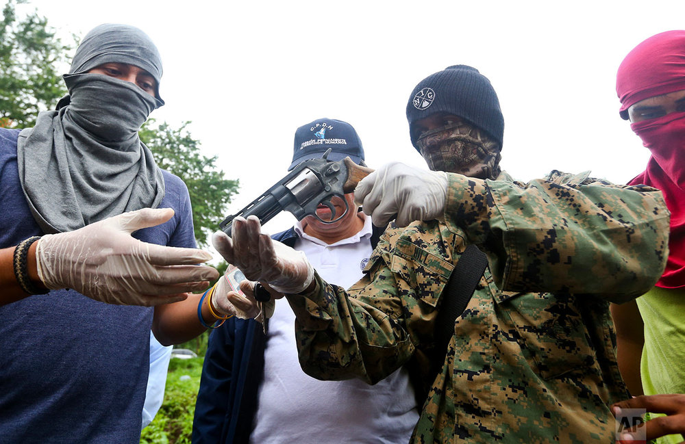 In this May 27, 2018 photo, masked show a weapon they say they seized from an attacker the previous night, at the Autonomous University of Nicaragua where anti-government students are barricading themselves on campus to protect themselves from government security forces and armed supporters in Managua, Nicaragua. (AP Photo/Esteban Felix)