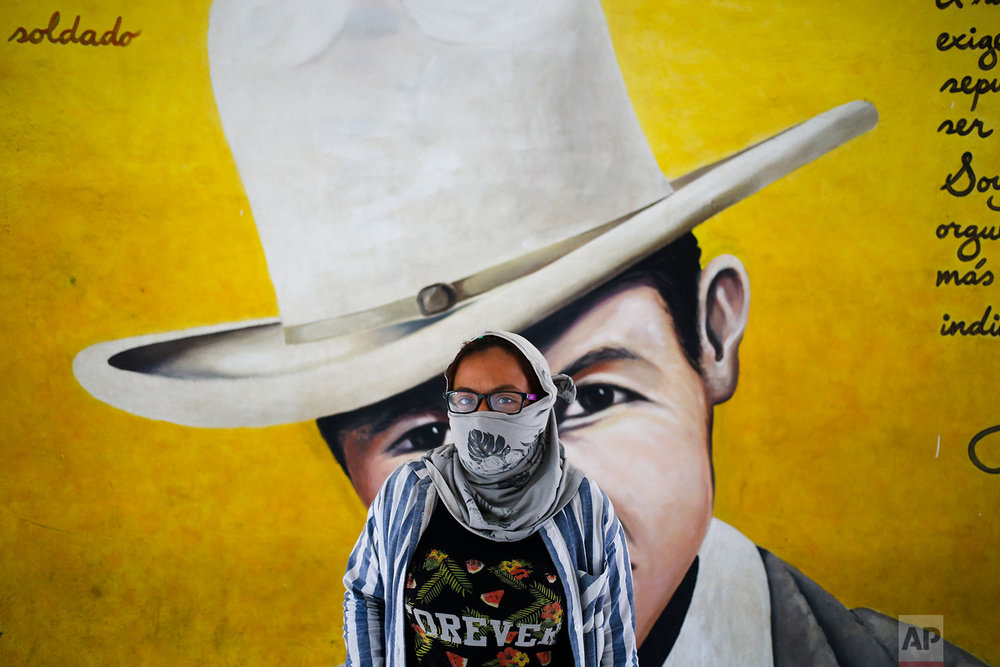 In this June 8, 2018 photo, an anti-government university student poses by a mural of national hero Augusto Sandino at the Autonomous University of Nicaragua school where students have barricaded themselves on campus for protection from government security forces and armed supporters in Managua, Nicaragua. (AP Photo/Esteban Felix)
