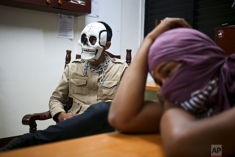In this June 7, 2018 photo, masked, anti-government university students of the Autonomous University of Nicaragua hold a meeting at the National Student Union office, a union associated with the ruling party, as they barricade themselves on campus for protection from government security forces and armed supporters in Managua, Nicaragua. (AP Photo/Esteban Felix)