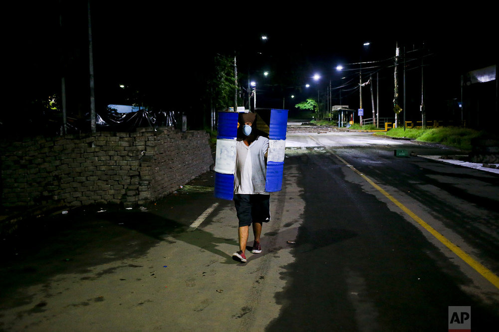 In this June 8, 2018 photo, an anti-government university student from the Autonomous University of Nicaragua walks outside the school carrying a metal trash barrel, cut in half and used as a shield, after a fellow student was shot to death at one of the entrances of the school where students have barricaded themselves inside for protection from government security forces and armed supporters, in Managua, Nicaragua. (AP Photo/Esteban Felix)