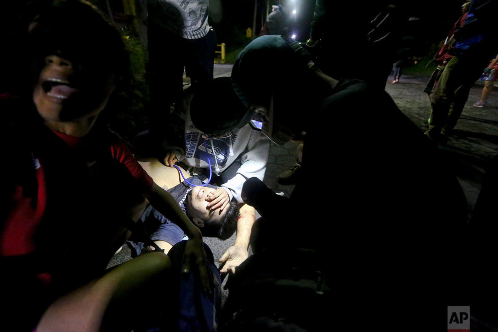 In this June 7, 2018 photo, high school student Chester Chavarria gets first aid by university students after he was shot at a barricade set up behind an entrance to the Autonomous University of Nicaragua, where anti-government students have barricaded themselves inside for protection from government security forces and armed supporters, in Managua, Nicaragua. (AP Photo/Esteban Felix)