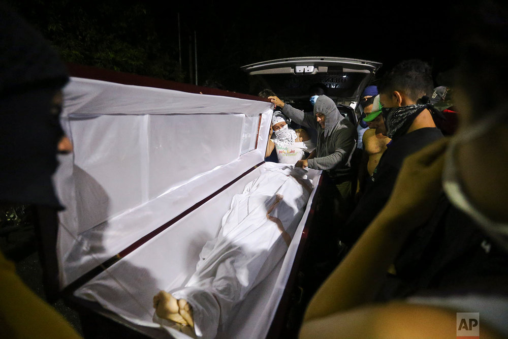 In this June 8, 2018 photo, students gather around the body of slain high school student Chester Chavarria one day after he was shot at the Autonomous University of Nicaragua where anti-government students have barricaded themselves on campus for protection from government security forces and armed supporters in Managua, Nicaragua. (AP Photo/Esteban Felix)