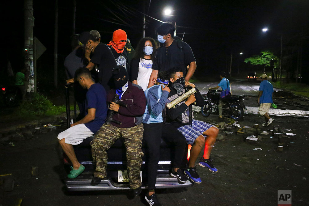 In this June 8, 2018 photo, friends of slain high school student Chester Chavarria ride on the back of a vehicle during his funeral procession from the Autonomous University of Nicaragua to his home for a wake in Managua, Nicaragua. (AP Photo/Esteban Felix)