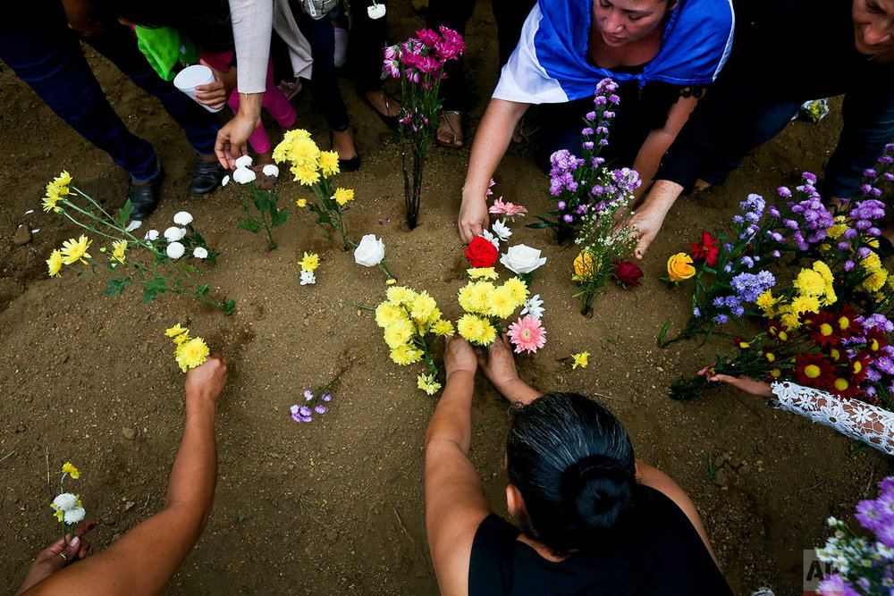 In this June 9, 2018 photo, relatives and friends of slain high school student Chester Chavarria place flowers on his grave after burying him in Managua, Nicaragua. (AP Photo/Esteban Felix)