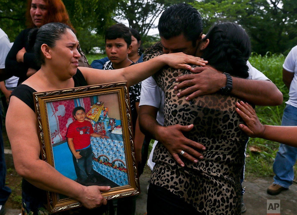 In this June 9, 2018 photo, the mother of slain high school student Chester Chavarria, right, is embraced by relatives during her son's burial service in Managua, Nicaragua. (AP Photo/Esteban Felix)
