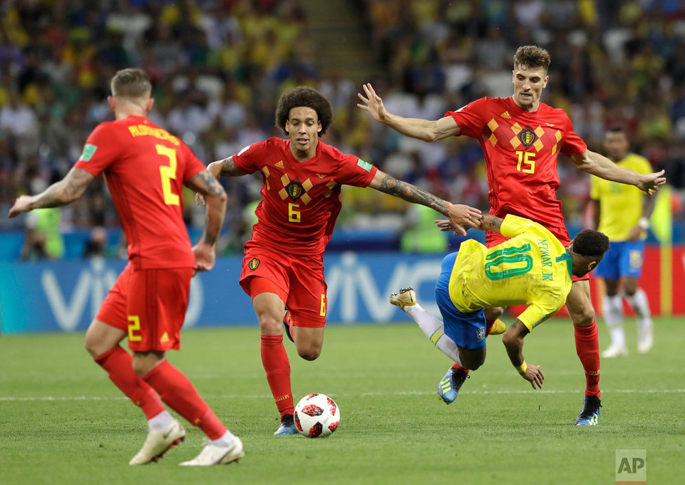 Brazil's Neymar takes a fall while battling Belgium's Axel Witsel, center, and Thomas Meunier, right, during the quarterfinal match between Brazil and Belgium at the 2018 soccer World Cup in the Kazan Arena, in Kazan, Russia, Friday, July 6, 2018. (AP Photo/Andre Penner)