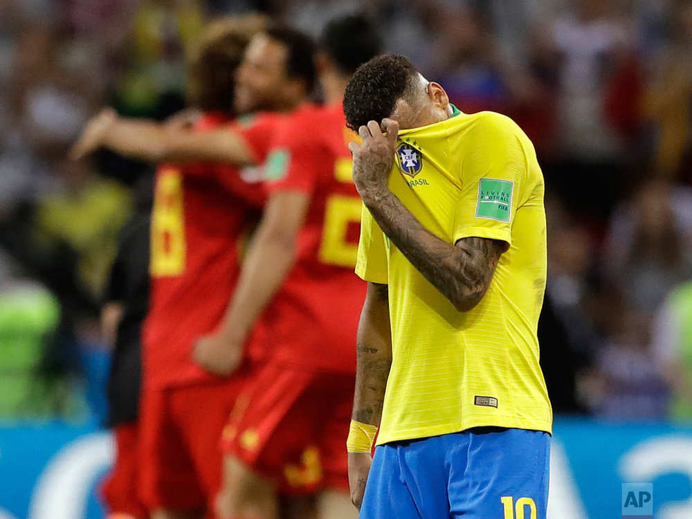Brazil's Neymar reacts as Belgium players celebrate after Brazil is knocked out by Belgium following their quarterfinal match at the 2018 soccer World Cup in the Kazan Arena, in Kazan, Russia, Friday, July 6, 2018. (AP Photo/Andre Penner)
