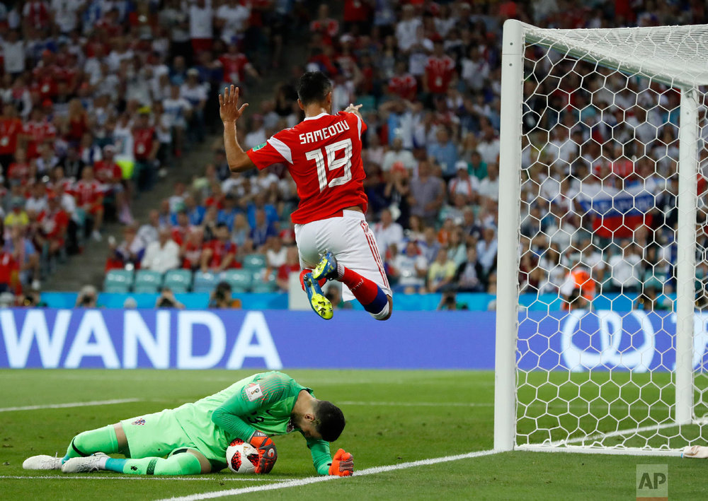 Croatia goalkeeper Danijel Subasic, left, makes a save in front of Russia's Alexander Samedov during the quarterfinal match between Russia and Croatia at the 2018 soccer World Cup in the Fisht Stadium, in Sochi, Russia, Saturday, July 7, 2018. (AP Photo/Rebecca Blackwell)