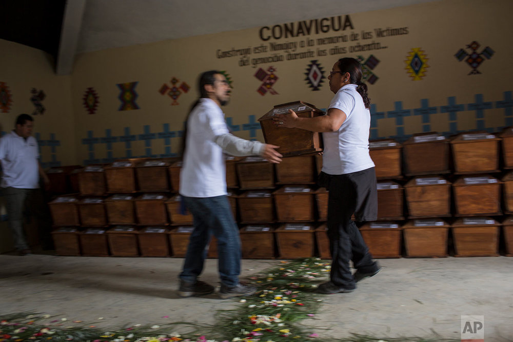 In this June 21, 2018 photo, forensic anthropologists organize the remains of 172 unidentified people who were exhumed from what was once a military camp, before properly burying them at the same spot where they were discovered in San Juan Comalapa, Guatemala. (AP Photo/Rodrigo Abd)