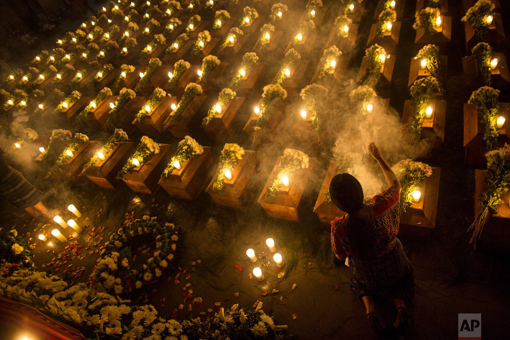 In this June 20, 2018 photo, a woman spreads incense over the coffins holding the remains of 172 unidentified people who were discovered buried at what once was a military camp in San Juan Comalapa, Guatemala, one day before their formal burial at the same site where they were discovered. (AP Photo/Rodrigo Abd)