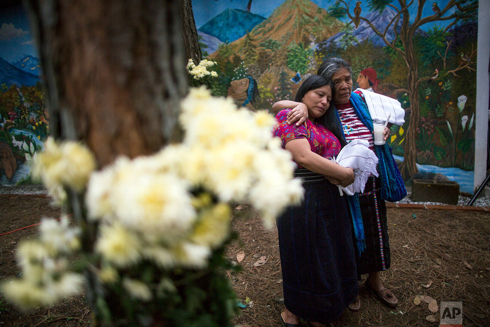 In this June 21, 2018 photo, women console each other during the former burial of 172 unidentified people who were exhumed from what was once a military camp, at the same site they were discovered in San Juan Comalapa, Guatemala. (AP Photo/Rodrigo Abd)