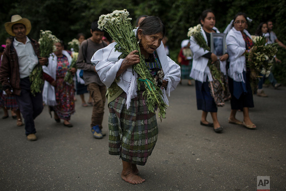 In this June 21, 2018 photo, an elderly woman walks barefoot to what was once a military camp during the funeral procession for 172 unidentified people who were exhumed from the camp and will be properly buried there in San Juan Comalapa, Guatemala. (AP Photo/Rodrigo Abd)