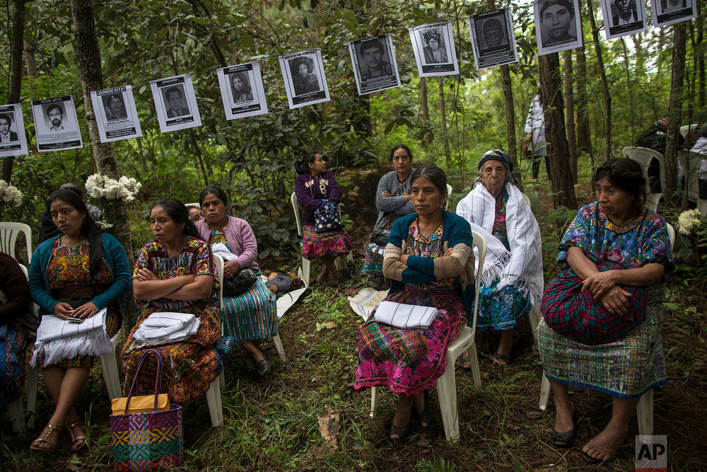 In this June 21, 2018 photo, women sit under the portraits of villagers who disappeared during the civil war as they attend the burial of 172 unidentified people who were exhumed from this area, once a military camp, in San Juan Comalapa, Guatemala. (AP Photo/Rodrigo Abd)