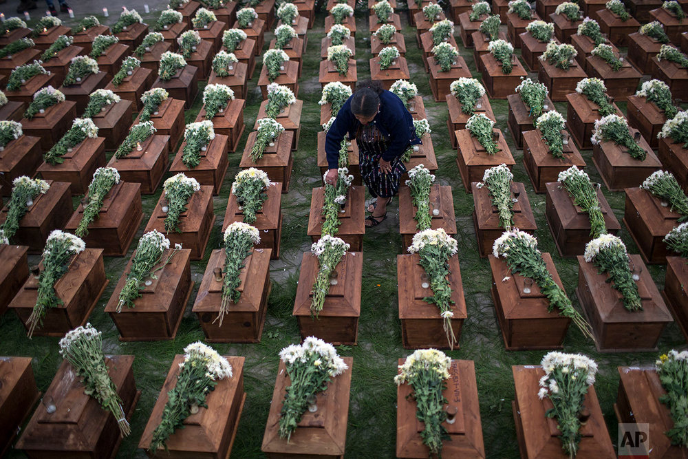 In this June 20, 2018 photo, a woman places flowers on coffins holding the remains of 172 unidentified people who were exhumed from what was once a military camp, during a funeral ceremony in San Juan Comalapa, Guatemala, one day before their proper burial. (AP Photo/Rodrigo Abd)