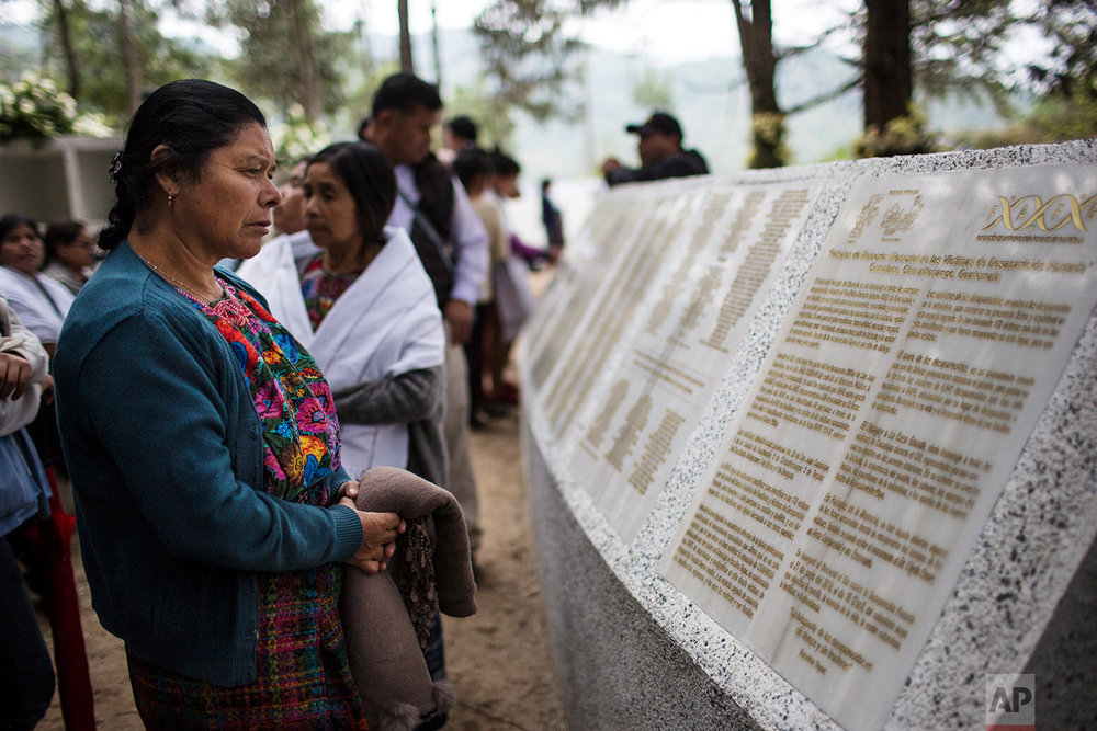 In this June 21, 2018 photo, a woman reads the names of people who disappeared during the civil war, at the site where a military camp once operated and where the 172 bodies were unearthed in San Juan Comalapa, Guatemala. (AP Photo/Rodrigo Abd)