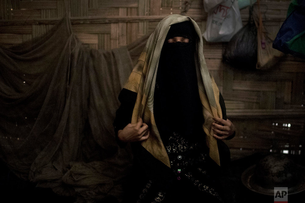 """A 13-year old Rohingya Muslim girl who agreed to be identified by her first initial, """"A,"""" adjusts her head scarf in her family's shelter in Jamtoli refugee camp in Bangladesh, June 26, 2018. (AP Photo/Wong Maye-E)"""