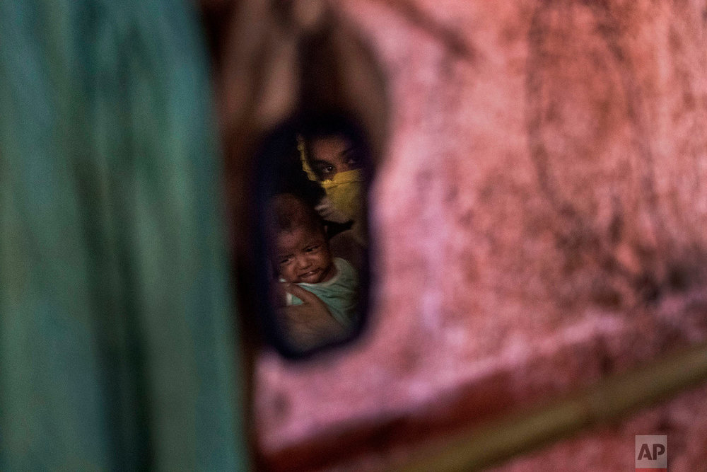 """M"" is seen carrying her baby boy in a reflection off a mirror hanging in her shelter in Kutupalong refugee camp in Bangladesh, June 26, 2018. (AP Photo/Wong Maye-E)"