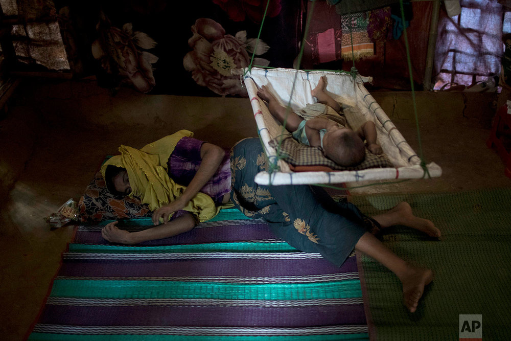 """""""M"""" lays on the floor of her shelter, uninterested in her baby boy who had awoken from his sleep, in Kutupalong refugee camp in Bangladesh,June 26, 2018. (AP Photo/Wong Maye-E)"""