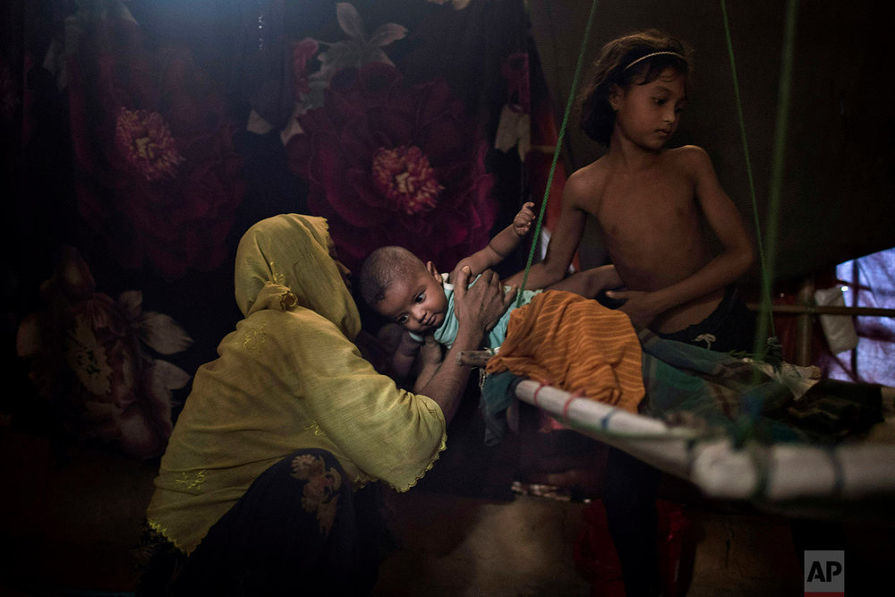 """""""M's"""" daughter, right, hands over her baby brother to their mother in their shelter in Kutupalong refugee camp in Bangladesh, June 26, 2018 . (AP Photo/Wong Maye-E)"""